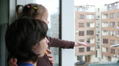 Mother and little child daughter stay by window watching catching rain drops  Stock Footage
