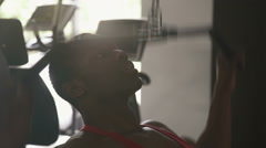 Close-up of black african-american bodybuilder training on apparatus in gym hall - stock footage
