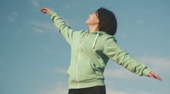 Young beautiful and smiling asian woman stretching on the blue sky background Stock Footage