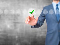 Businessman check mark on virtual screen. Finger on a checklist box and ticki Stock Photos
