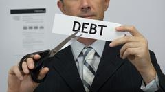 Businessman Cuts Debt Concept - stock photo
