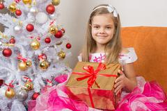 girl in a beautiful dress gave New Year gift - stock photo