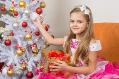 Seven-year girl in a beautiful dress sits with a gift and holding a Christmas Kuvituskuvat