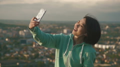 Lovely young japanese woman taking selfie and making funny faces outdoor in park - stock footage