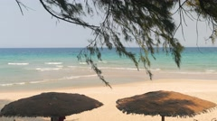 Beautiful tropical empty beach scene with two umbrellas Stock Footage