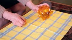 Old woman at home removing money from a piggy bank and counting coins - stock footage