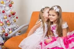 Two girls in beautiful dresses whispering sitting on couch at Christmas tree Kuvituskuvat