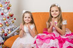 Two girls in beautiful dresses guessing gifts for the new year Kuvituskuvat