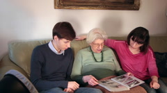 Grandmother showing a photo album to her happy family Stock Footage