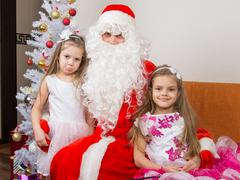 Two girls in beautiful dresses hug Santa Claus sitting on the couch, one of t Kuvituskuvat