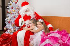 Two girls in beautiful dresses hug Santa Claus Kuvituskuvat