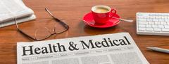 A newspaper on a wooden desk - Health and Medical - stock photo