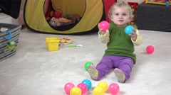 Cute little girl eating crackers and playing with colorful balls Stock Footage