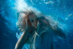 Woman with long blonde hair underwater. Stock Photos