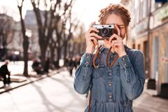 Concentrated woman taking pictures outdoors using old vintage camera Stock Photos