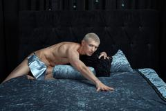 Metrosexual man on the bed. - stock photo