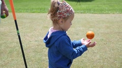Little child kid girl play catching a toy golf ball in a park Stock Footage