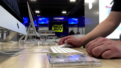 Man browsing website on display iMac computer inside Best buy store - stock footage