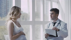 Pregnant woman visiting young doctor, dolly shot - stock footage