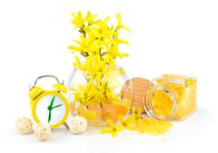 Composition from spring yellow flowers, aroma salt and alarm clock Stock Photos