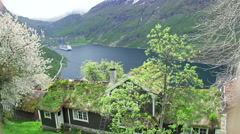 wooden house with a green roof in the fjord in the distance passenger ship - stock footage
