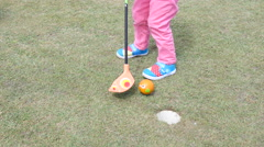 Little girl legs - playing golf for children striking a ball in a hole - stock footage
