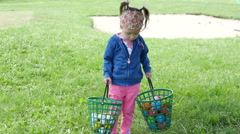 Children on a golf field - little girl play walk with balls in buckets - stock footage