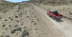 Car traveling through dirt road in a dry, desertic, mountainous landscape. Stock Footage