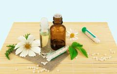 Homeopathic medication with flowers and leaves - stock photo