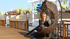 Woman sitting on a wicker swing, aqua park in background Stock Footage