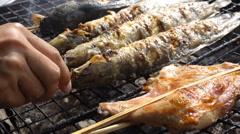 Grilled catfish on the stove, street market in Thailand - stock footage