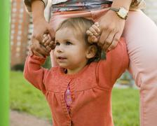 Little girl with mother outside walking on playground, holding hands, lifestyle Stock Photos