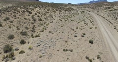Dry, desertic, mointainous landscape. High visual of landscape with dirt road. Stock Footage