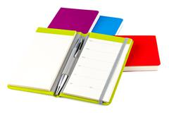Colourful notebooks with ballpoint pen - stock photo