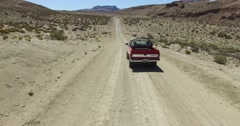 Car traveling through dirt road in dry, desertic, mountainous landscape. Stock Footage