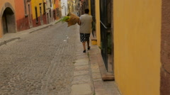 An elderly woman carries a bouquet of flowers down a colonial street - stock footage