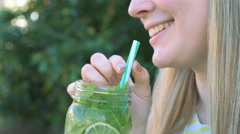 Happy teen drinking lemonade with lime and mint Stock Footage