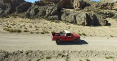 Car traveling through dirt road in a dry, desertic, rocky, mountainous landscape Stock Footage