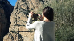 Young woman taking photo with cellphone in the mountains, super slow motion Stock Footage
