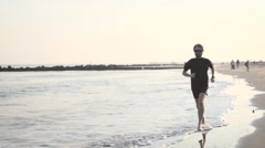 A man runs on the beach at sunset - 240 fps slow motion Stock Footage