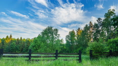 4k timelaspe of green meadow and wooden fence near forest at sunset Stock Footage