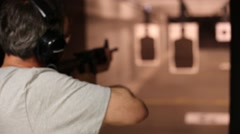 A young man shooting an AR 15 semi automatic rifle at an indoor shooting range Stock Footage