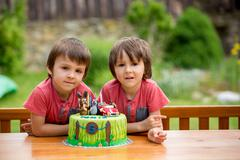 Beautiful adorable five year old boy, celebrating his birthday, blowing candl - stock photo
