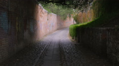 Camera moving from dark to light in a corridor or alley Stock Footage