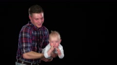 Affectionate father playing with baby son at home - lifting him - stock footage