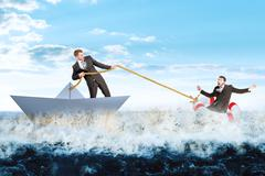 Businessman in paperboat save scared man Stock Photos