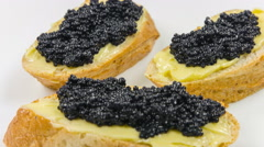 Close-up of canapes with butter and black caviar. - stock footage