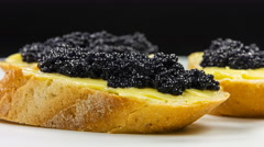 Sandwiches with butter and black caviar on black background, macro shoot. Stock Footage