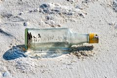 Real message in a bottle abandoned on sandy beach close up Stock Photos