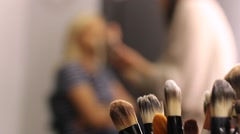 A make up artist preparing a woman for her appearance - stock footage